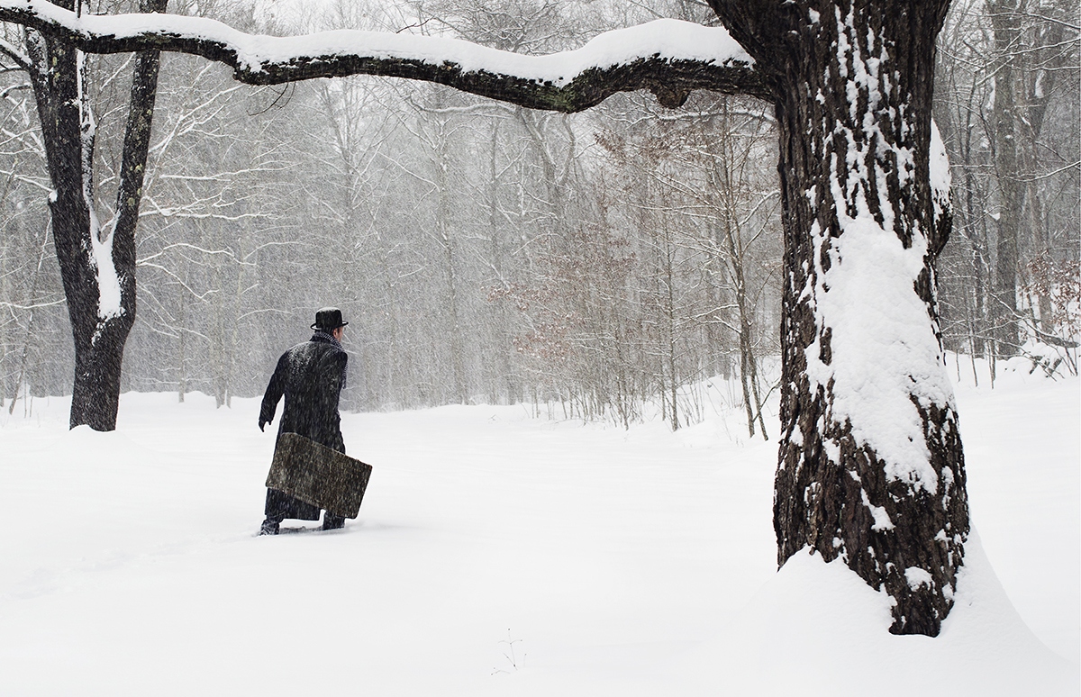 man with suitcase walking in snow