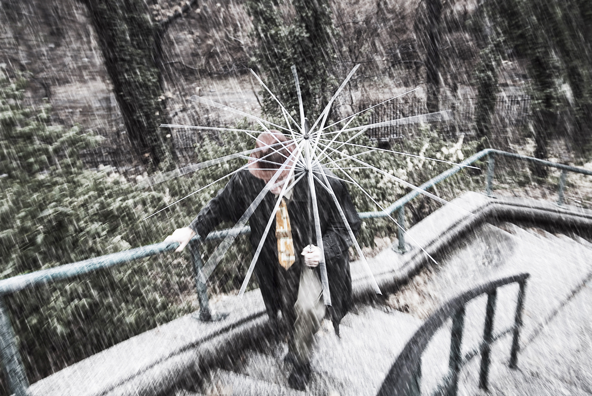 man with broken umbrella
