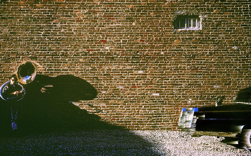 Tuba player at brick wall